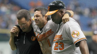 April 4, 2012; St. Petersburg, FL, USA; Baltimore Orioles second baseman Brian Roberts (1) is carried off the field by the trainer and first base coach Wayne Kirby (23) after he hurt his knee sliding into second base during the ninth inning against the Tampa Bay Rays at Tropicana Field. Baltimore Orioles defeated the Tampa Bay Rays 6-3. Mandatory Credit: Kim Klement-USA TODAY Sports